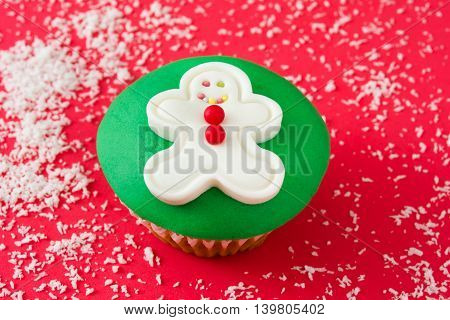 Sweet gingerbread man cupcake on red background