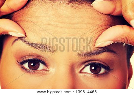 Woman checking her wrinkles on her forehead