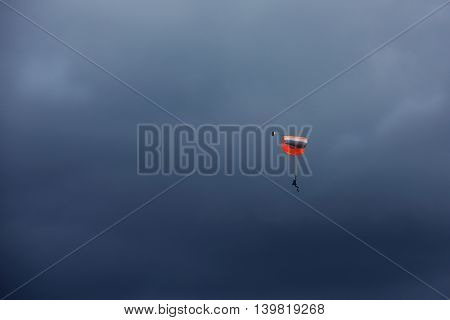 2 landing parachutiss in cloudy sky background.One parachute, landing parachutist, Skydiver with parachute open landing, Paragliding over the clouds against blue sky Paraglider flying in the blue sky with clouds backgrounds,sunset, Lithuania,sport