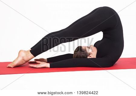 Beautiful athletic girl in a black suit doing yoga. halasana asana - plow pose . Isolated on white background.