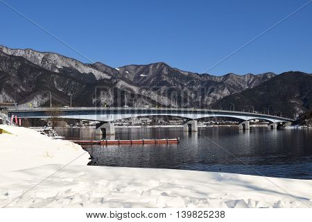 Lake Kawaguchiko Ohashi Bridge, Japan.  'Ohashi' translates to 'big bridge'.  Snow covered banks of Lake Kawaguchiko and mountain background.