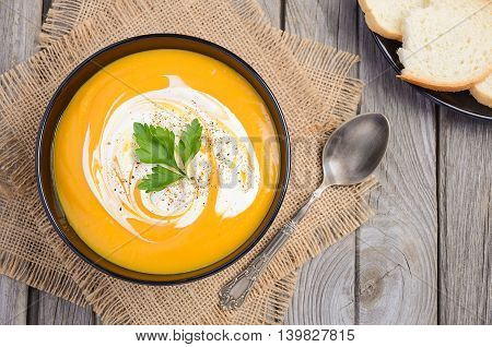 Pumpkin soup with cream and parsley on wooden background, top view, copy space