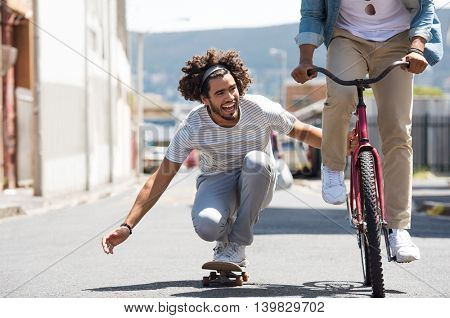 Closeup of a happy young man skateboarding with help of friend bicycle. Smiling guys having fun with skate board and cycle. African man riding a bike while his friend attacking with skateboard.