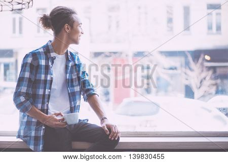 About future. Smiling and confident young man sitting on a window sill while being in a cafe