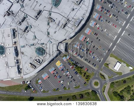 Supermarket roof and many cars in parking viewed from above.
