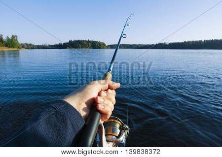 Fishing on a lake at sunset. Fishing rod with a reel in hand.