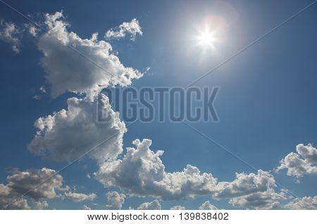 Chain of cumulus clouds with sun. Blue sky.
