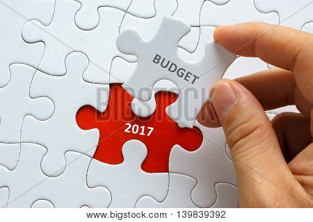 Hand holding piece of blank jigsaw puzzle with word BUDGET 2017. poster