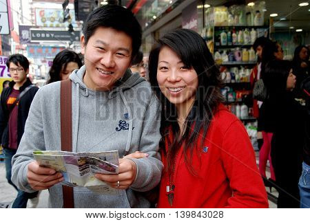 Hong Kong China - January 22 2007: Young couple check their Hong Kong map while strolling on Nathan Road in Kowloon