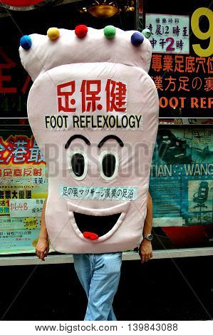 Hong Kong China - August 17 2006: Man dressed in a foot costume advertising a foot reflexology spa on Nathan Road in Kowloon