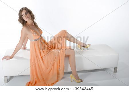 Cute Girl In A Peach Dress Leans On A Sofa