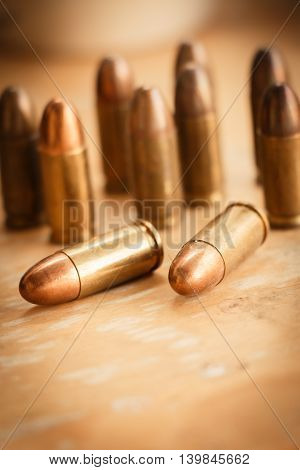 11mm bullets and short gun on brown background. (selective focus)