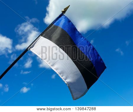 Close-up of the Estonian flag, symbol of freedom and representing one of the Baltic countries, held up against a blue sky with a few clouds for contrast.