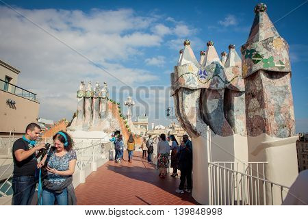 Barcelona Spain - October 27 2015: Tourists watch colorful chimneys on the roof of Casa Batllo one of Antoni Gaudi's architectural masterpieces in Barcelona.