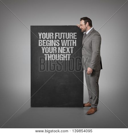 Your future begins with your next thought text on blackboard with businessman standing side