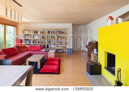 Living room of an eco house, red divan and fireplace