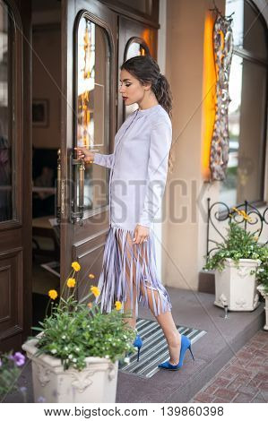 Stylish model in the lilac jacket and blue shoes stands sideways near the entrance to the cafe. She holds the right hand on the door handle. Her eyes are closed. Outdoors. Vertical.