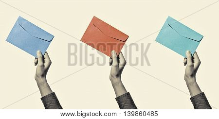 Set of three images of a hand with envelope of different colors isolated toned black and white