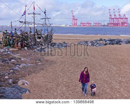 NEW BRIGHTON, ENGLAND, JUNE 29. Magazines Promenade on June 29, 2016, in New Brighton, England. A young mother and her son walk near the Black Pearl art installation in New Brighton England