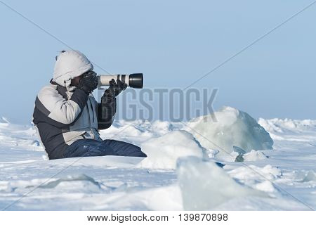 The photographer is photographing with telephoto lens in the Arctic ice.