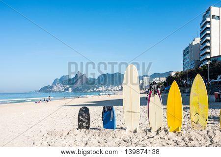 Surfboards standing upright in bright sun on the Ipanema beach Rio de Janeiro Brazil