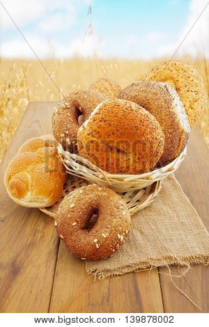 Freshly baked bread and buns on wooden table over wheat field