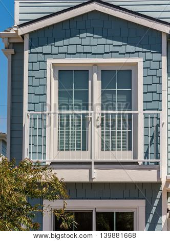Pale blue shakes shingle siding fake balcony and double full lite door