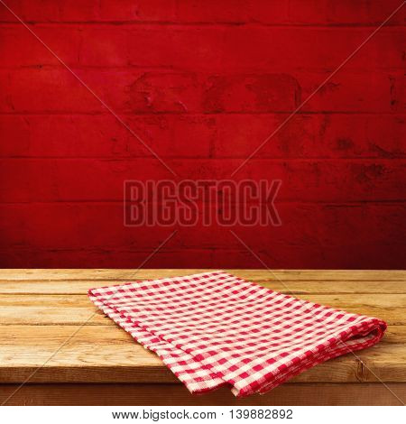 Vintage wooden table with tablecloth over red brick stone wall