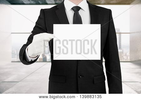 Business man holding blank card on interior with city view background. Mock up