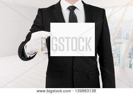 Business man holding blank card on white interior background. Mock up