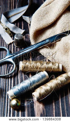 Sewing textile or cloth. Scissors reel of thread, and golden fabric. Work table of a tailor.