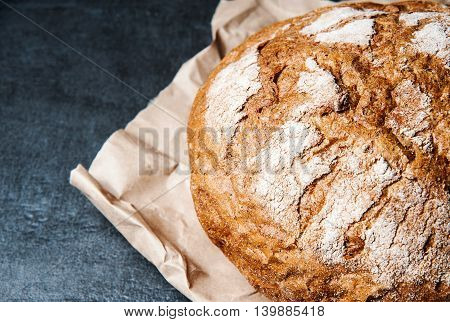 loaf of bread on paper on dark table closeup