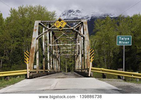 Skagway Alaska USA--April 29 2016 Rusty Steel Bridge over the Taiya River in Skagway Alaska
