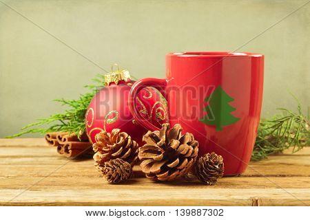 Christmas mug with pine corns and ornaments on wooden table
