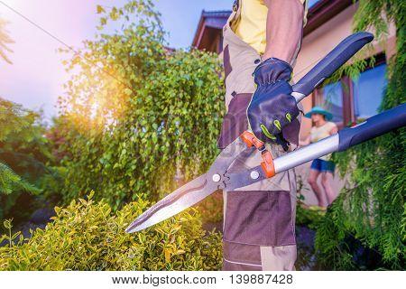 Professional Gardener with Large Scissors Preparing For Garden Work.