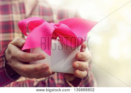 person holds holiday gift tied with a ribbon / time to give and receive gifts