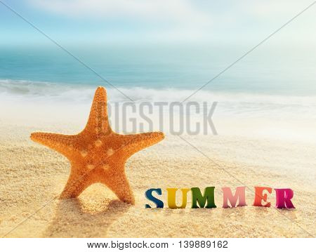 Summer beach. Word summer of color letters on summer beach and starfish on a background of ocean.