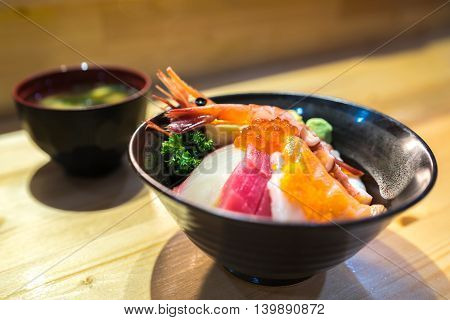 Chirashi sushi Japanese food rice bowl with raw salmon sashimi scallop shrimp surf clam salmon eggs octopus tuna hamachi and sweet scrambled egg served with miso soup focus on salmon eggs with depth of field effect