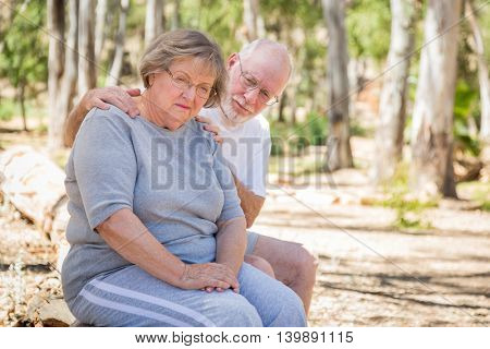 Very Upset Senior Woman Sits With Concerned Husband Outdoors.