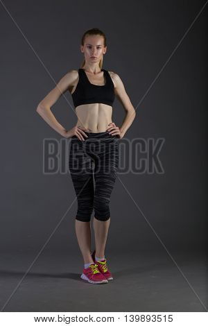 Body of slim female in activewear doing posin on gray low key perfect sport woman