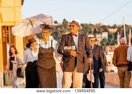 Piran, Slovenia - May 8, 2016: Elder couple in traditional slovenian costumes walk during Tartini Festival in Piran. The Tartini Festival is an music festival dedicated to maestro Giuseppe Tartini.