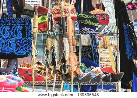 Various of Kazakh traditional souvenirs ethnic hats shoes and horsewhip with ornaments in market in Kok-tobe park Almaty Kazakhstan poster