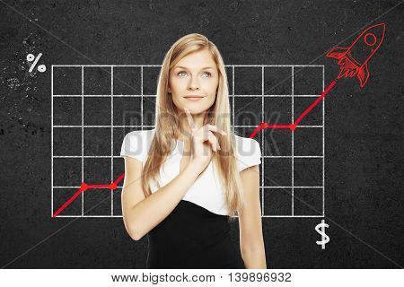 Start up concept with pretty thoughtful businesswoman. Business chart with red rocket ship on concrete wall in the background