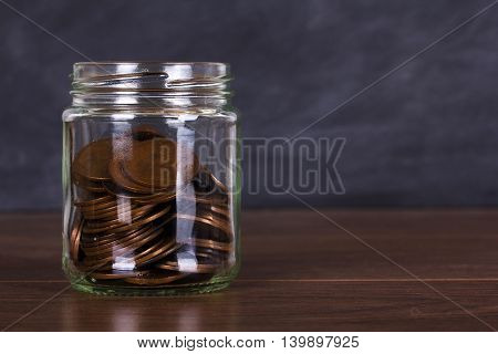 Glass Jar On Wooden Surface Filled With Old Coins