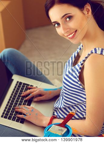 Young woman portrait while painting new apartment , sitting with laptop