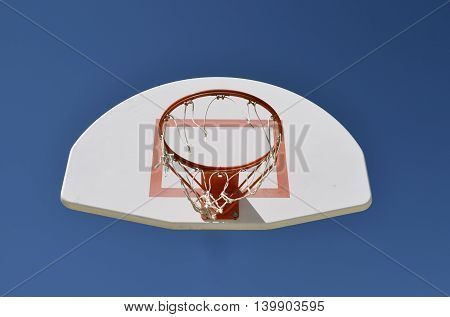 A basketball hoop with a ripped net and white backboard appear to be floating in the air.