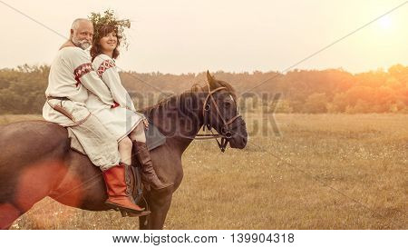 Mature Man And Woman Are Riding A Horse On The Rural Summer Background.