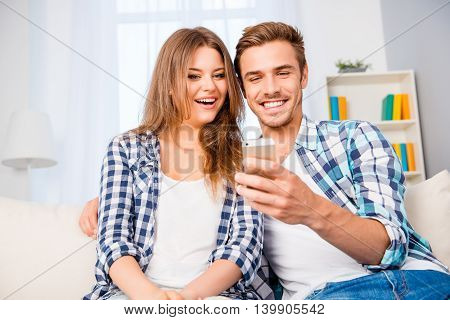 Smiling Man Showing Sms On Mobile Phone To His Excited Wife