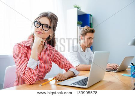 Portrait Of Woman Dreaming While Her Partner Working With Laptop