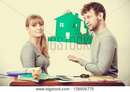 Ecology in practical domestic life. People real estate and house concept. Young couple with green ecological paper house happily thinking of future.
